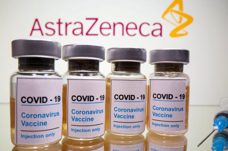 "Vials with a sticker reading, ""COVID-19 / Coronavirus vaccine / Injection only"" and a medical syringe are seen in front of a displayed AstraZeneca logo in this illustration taken October 31, 2020."